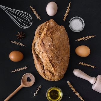 Pan fresco rodeado de varios ingredientes para hornear y utensilios sobre fondo negro