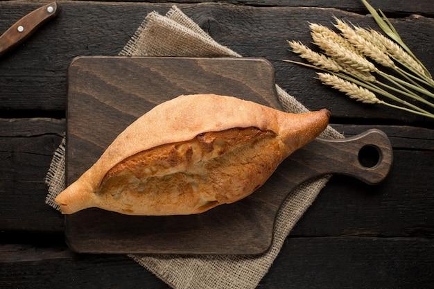 Pan fresco en un tablero con trigo en la madera