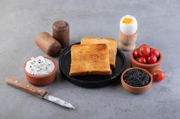 Pan frito con caviar y tomates cherry rojos colocados sobre superficie de mármol.