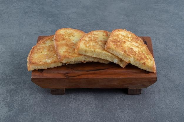 Pan frito con huevo sobre tabla de madera.