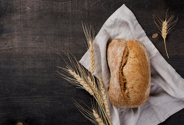 Pan con granos y trigo sobre tela