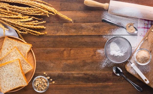 Pan horneado en bandeja de madera e ingrediente para cocido, vista superior con espacio de copia