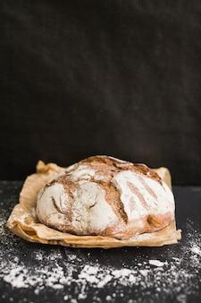 Pan horneado casero rústico en papel marrón sobre fondo negro