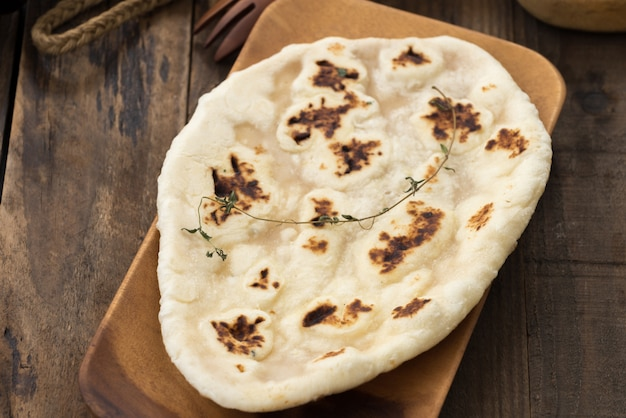 Pan indio de ajo naan en madera