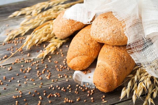 Pan integral de avena y harina de trigo sarraceno con picos en la mesa de madera vieja.