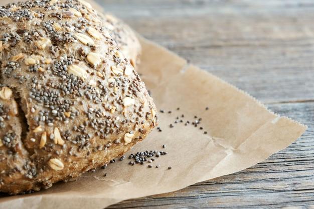 Pan integral de centeno con semillas de girasol, chía y copos de avena sobre papel de hornear. de cerca. lugar para el texto