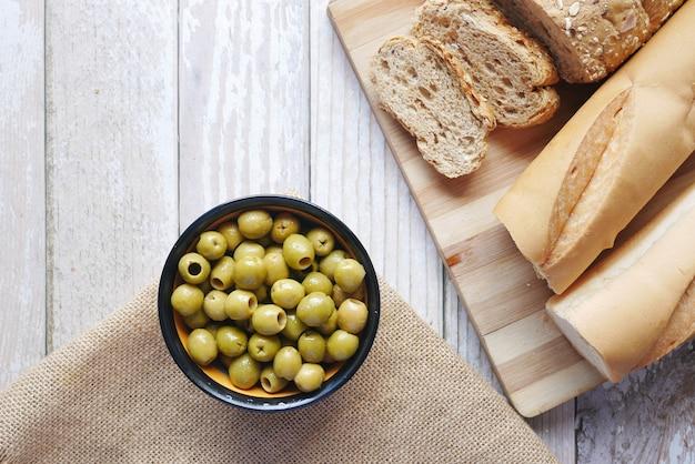 Pan integral y cuenco de aceitunas en la mesa