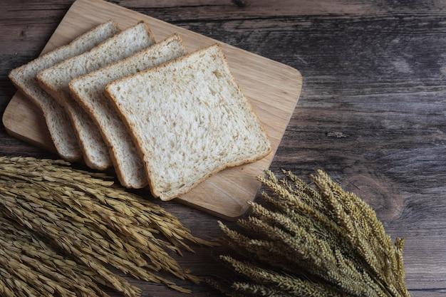 Pan integral o pan integral en mesa de madera con espiga de arroz