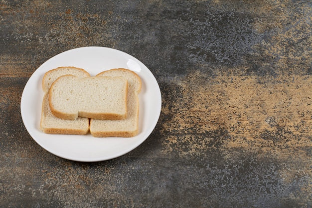 Pan integral en rodajas en un plato blanco.