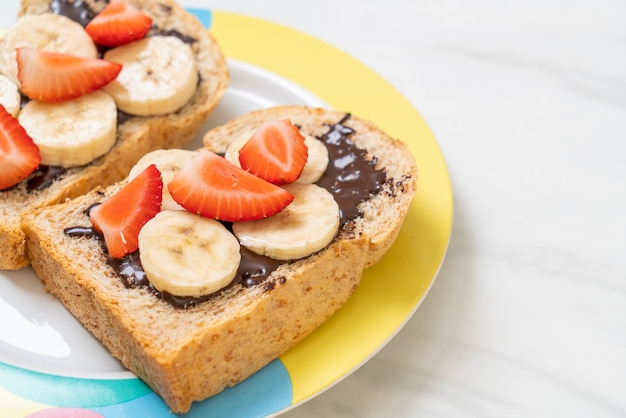 Pan integral tostado con plátano fresco, fresa y chocolate para el desayuno