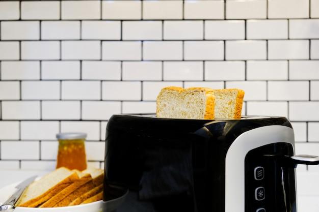 Pan integral en una tostadora con mermelada de naranja para un desayuno saludable en casa fondo de pared de ladrillo blanco