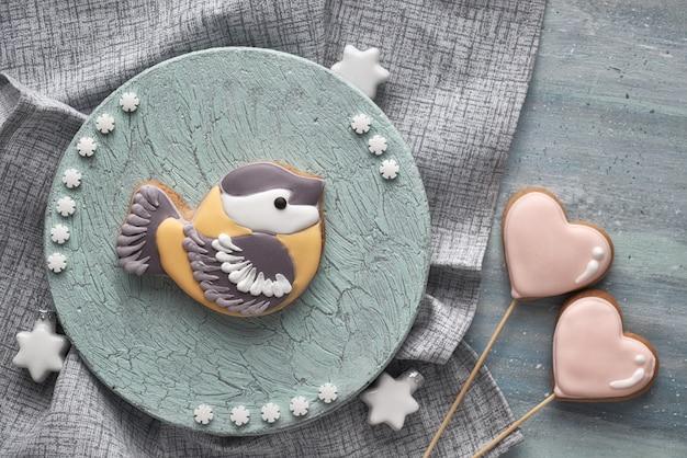 Pan de jengibre con forma de pájaro tit en tablero azul claro con estrellas blancas y corazones de pan de jengibre