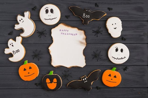 Pan de jengibre de halloween y arañas decorativas alrededor de papel ardiendo