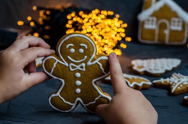 Pan de jengibre de navidad con azúcar glas blanco pintado sobre un fondo oscuro.