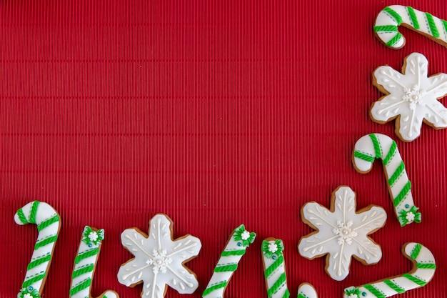 Pan de jengibre de navidad pintado a mano verde y blanco bastón de caramelo y copos de nieve sobre un hermoso fondo rojo. concepto de tarjeta vista superior. endecha plana.
