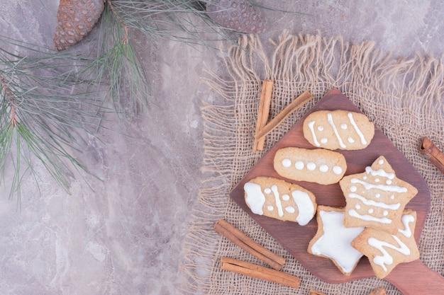Pan de jengibre navideño en forma de estrella y ovale sobre una tabla de madera con ramas de canela alrededor