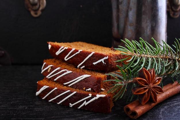 Pan de jengibre (pastel de miel) con pasas adornadas con glaseado, ramas de abeto, palitos de canela, anís estrellado sobre un fondo negro