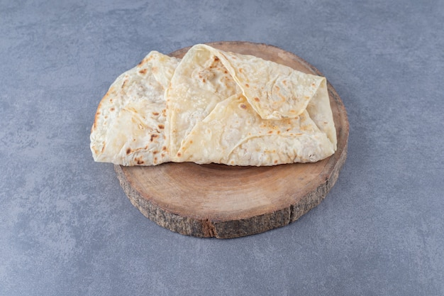 Pan de lavash en una placa sobre mesa de mármol.