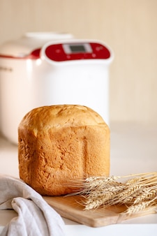 Pan de una máquina de hacer pan con espiguillas de trigo sobre una tabla con una servilleta de cocina