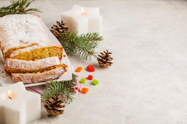 Pan de navidad con frutas confitadas y azúcar en polvo en decoraciones de navidad.