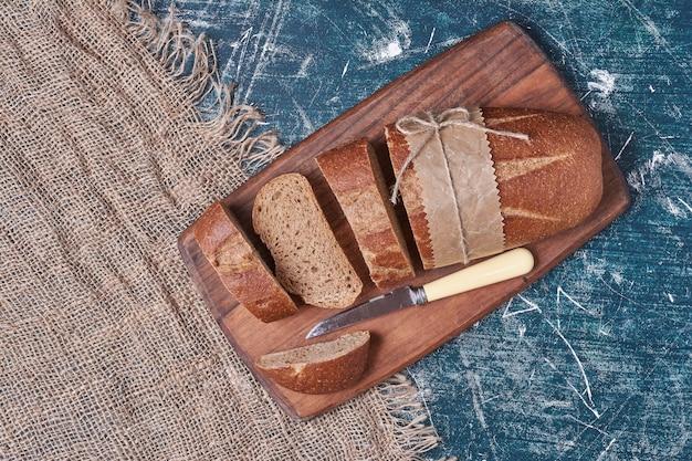 Pan negro artesanal sobre tabla de cortar.