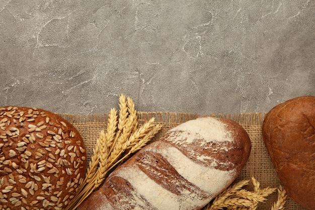 Pan oscuro fresco con espiguillas de trigo sobre mesa de hormigón gris. vista superior