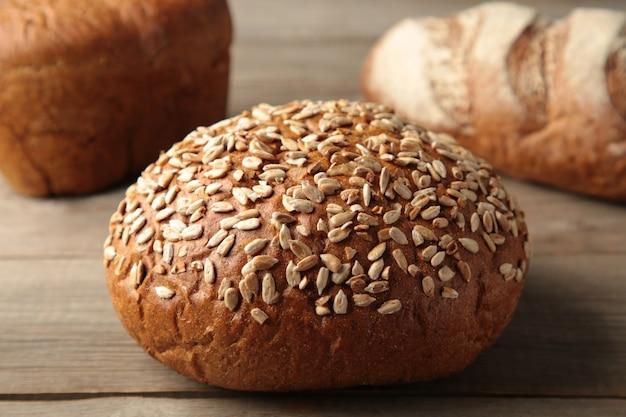 Pan oscuro fresco con espiguillas de trigo sobre mesa de madera gris. vista superior