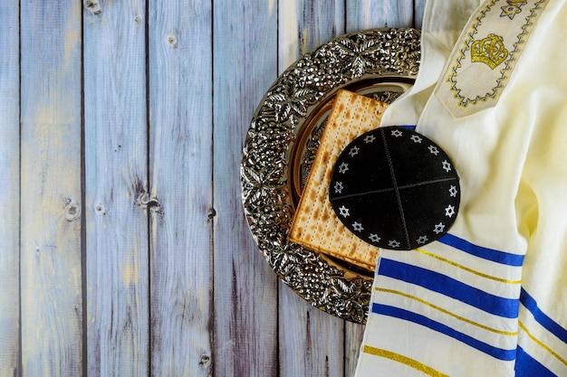 Pan de pascua judía matzoh en el plato tradicional del séder con kipah y tallit