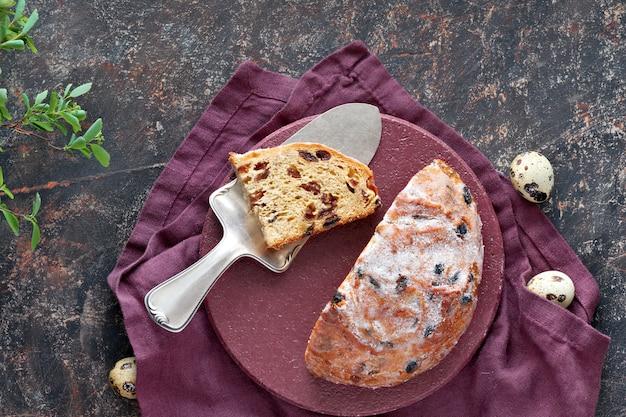 Pan de pascua (osterbrot en alemán). vista superior del pan fruty tradicional en mesa oscura con hojas frescas y huevos de codorniz