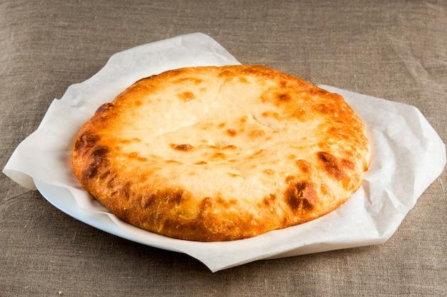 Pan de pita, pizza de calzone, fondo de tela sobre tela de lino