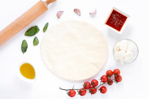 Pan plano crudo de la pizza e ingrediente sabroso aislados en el fondo blanco