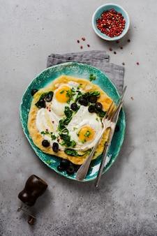 Pan plano de huevos turcos con yogur, queso, aceitunas, espinacas y pimiento rojo en placa vintage de cerámica