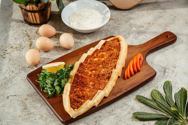 Pan plano de pide turco con carne picada y cobertura de tomate