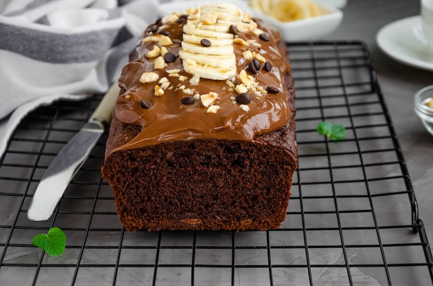 Pan de plátano con chocolate casero con crema de chocolate, rodajas de plátano y nueces encima sobre un fondo de hormigón oscuro. orientación horizontal.