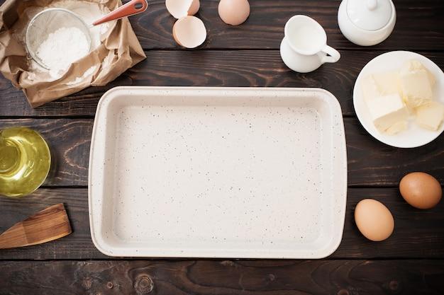 Pan y productos para su preparación de masa sobre fondo de madera oscura