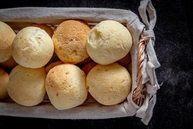 Pan de queso casero brasileño, también conocido como 'pao de queijo' en una cesta rústica.