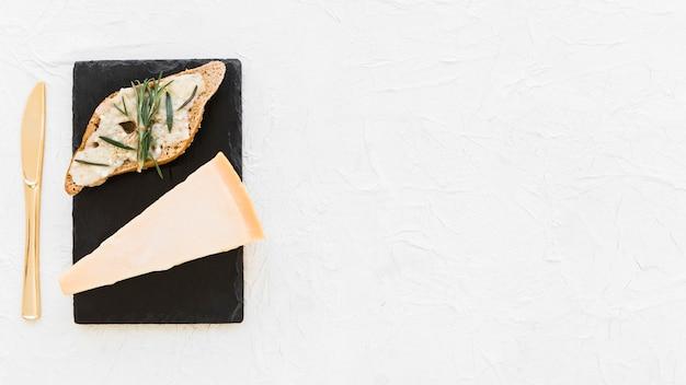 Pan con queso cheddar triangular en placa de pizarra sobre el fondo blanco