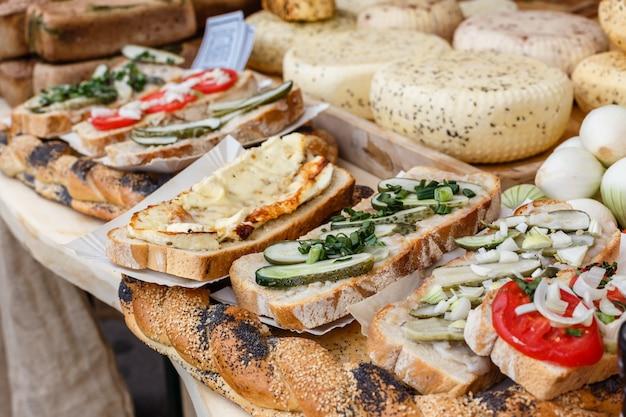 Pan con queso, pepinos, tomates en la mesa de picnic
