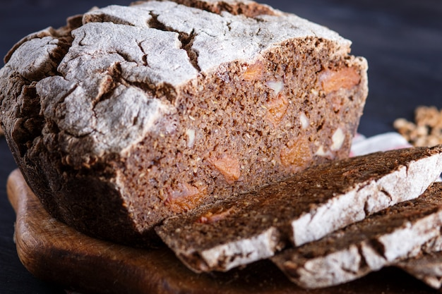 Pan rebanado casero sin levadura con centeno entero y granos de trigo sobre fondo de madera negra