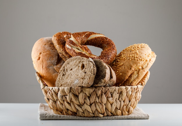 Pan rebanado con vista lateral de bagel turco sobre una superficie blanca y gris