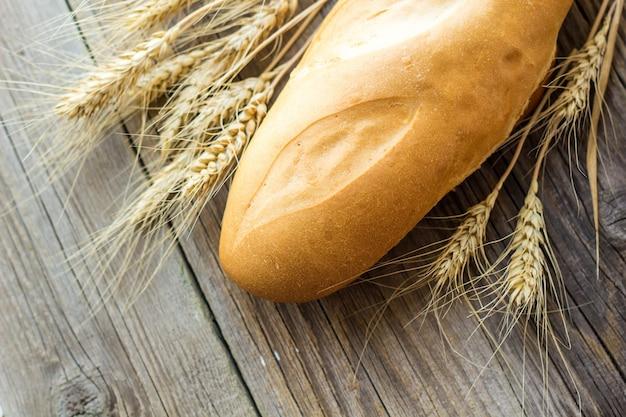Pan recién horneado y espigas de trigo en la mesa de madera