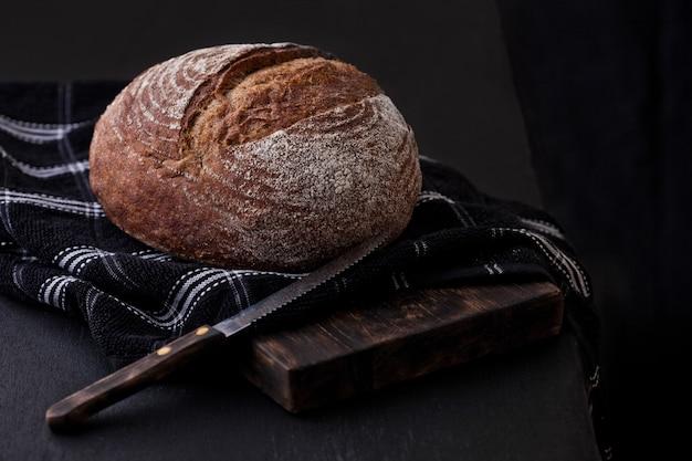 Pan recién horneado con papel de cocina y cuchillo sobre tabla de madera oscura