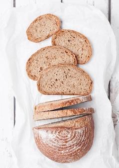 Pan recién horneado con trozos sobre tabla de madera blanca