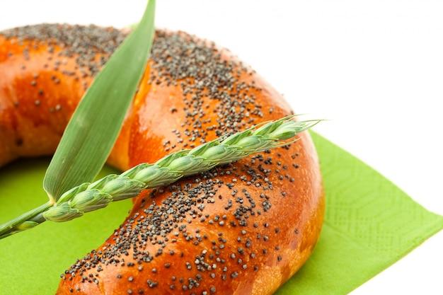 Pan con semillas de amapola y oreja aislado en blanco