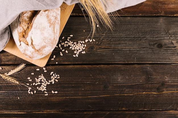 Pan con semillas de girasol y cosecha de trigo en mesa de madera