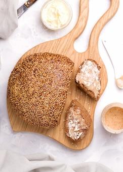 Pan con semillas de sésamo sobre una tabla de madera junto a trozos cortados con mantequilla de maní con mantequilla. desayuno