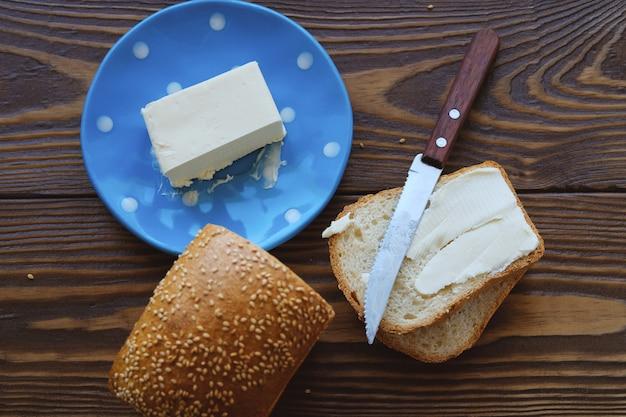 Pan con sésamo y mantequilla en una mesa de madera rústica. elaboración de tostadas y bocadillos para el desayuno o el almuerzo.