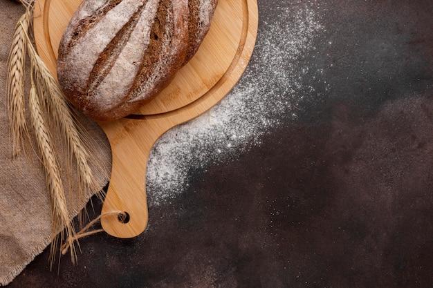 Pan sobre tabla de madera con trigo y harina