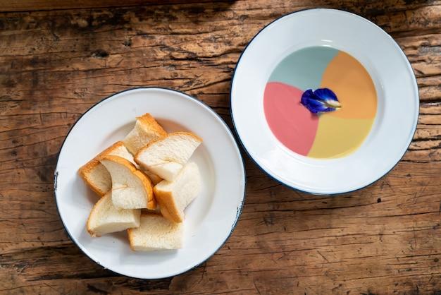 Pan tostado al vapor con natillas de colores sobre mesa de madera