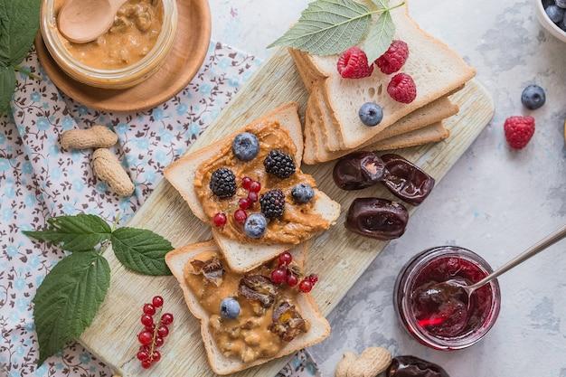 Pan tostado casero con mermelada y mantequilla de maní en la mesa de madera para el desayuno. delicioso pan tostado listo para servir. pan tostado con crema para el desayuno.